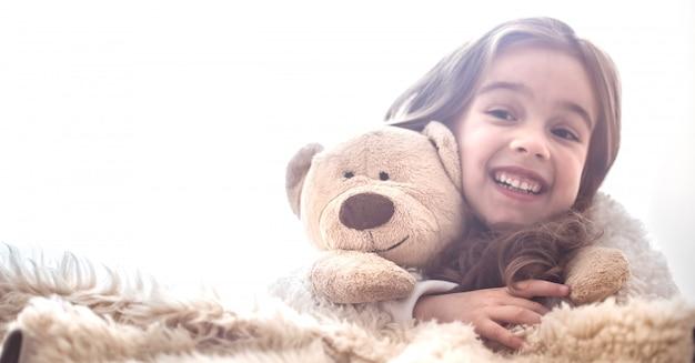 Маленькая девочка обнимает игрушку медведя
