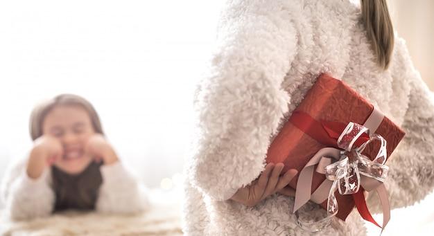 クリスマスのコンセプト、ママは小さなかわいい娘に贈り物を与える