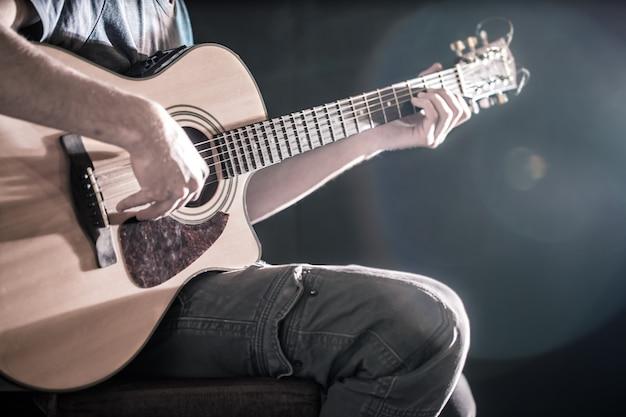 Рука человека играет на акустической гитаре, крупный план, вспышка света