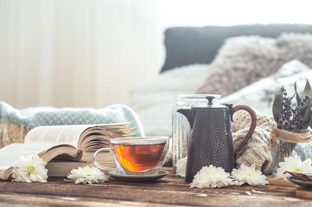 Натюрморт с деталями домашнего интерьера на деревянном столе с чашкой чая