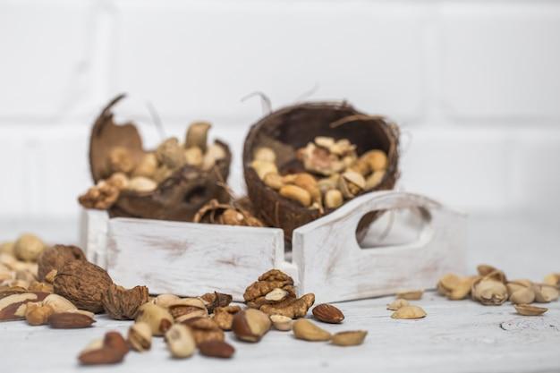 Разные орехи крупным планом на белом деревянном столе