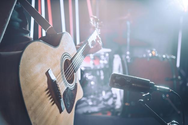 Студийный микрофон записывает акустическую гитару крупным планом.