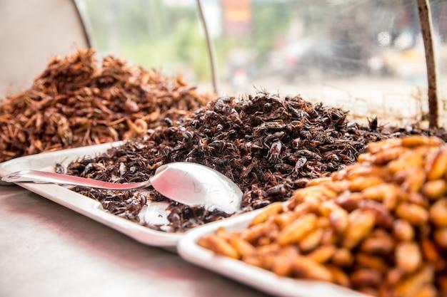 Тайская традиционная еда кузнечиков, личинок