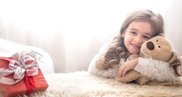 Рождество концепции маленькая девочка обнимает игрушку медведя