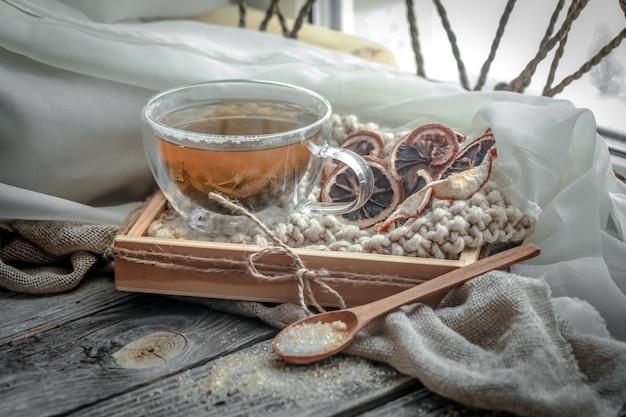 木製のテーブルにお茶の透明なカップのある静物