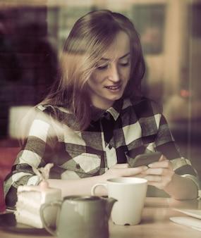Красивая девушка с телефоном в кафе за столом,