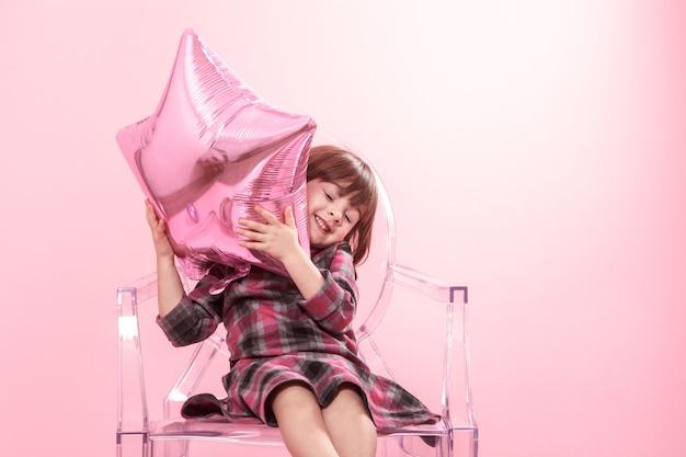 Маленькая девочка с удовольствием с воздушными шарами и конфетти. концепция праздника и веселья.