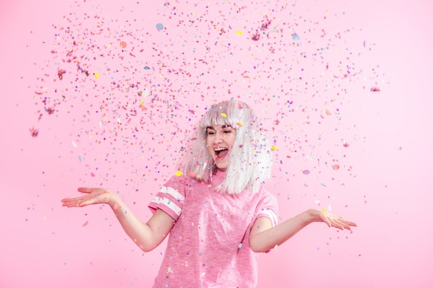 Смешная девчонка с серебряными волосами дарит улыбку и эмоции на розовой стене. молодая женщина или девушка с конфетти