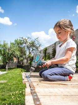 Маленькая девочка ремонтирует с отверткой и отверткой в руке