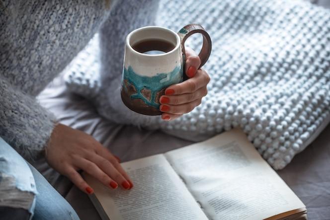 Девушка держит чашку и читает книгу