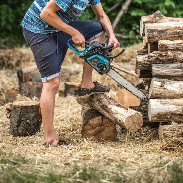 Мужчина рубит дрова бензопилой