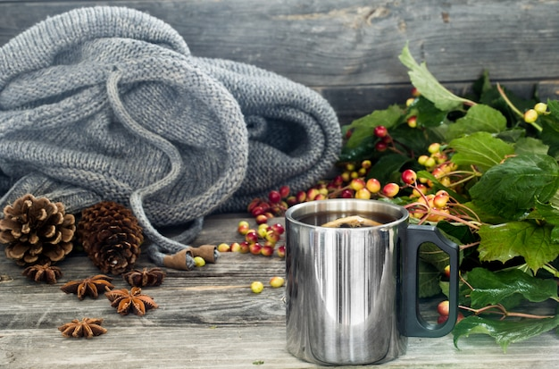 Чашка чая на красивом деревянном столе с зимним свитером, ягодами, осень