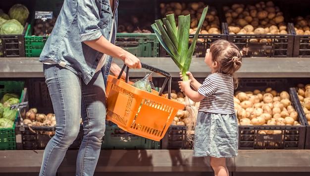 Мама и дочка делают покупки в супермаркете