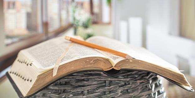 美しいテラスの背景に、鉛筆のクローズアップで聖書を予約します。モーニングタイム。
