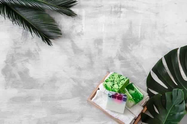 Спа. предметы по уходу за телом на белом фоне с тропическими листьями. летние аксессуары. пространство для текста.