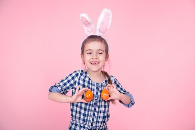 Портрет милой маленькой девочки с пасхальными яйцами на розовой предпосылке.