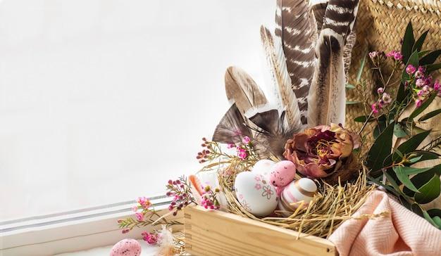 ハッピーイースターの背景。花の装飾と窓の近くの羽の巣でピンクのイースターエッグ