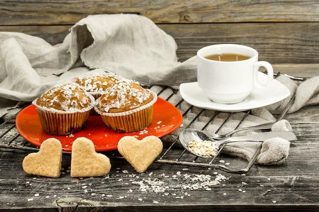 Красивые кексы с ягодами на деревянном фоне в красной тарелке