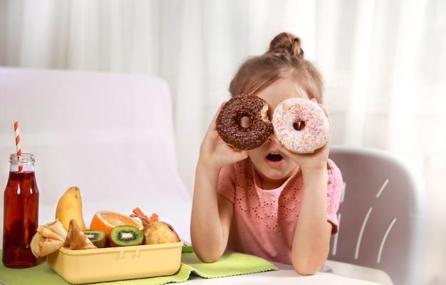 Маленькая красивая веселая девушка ест пончик