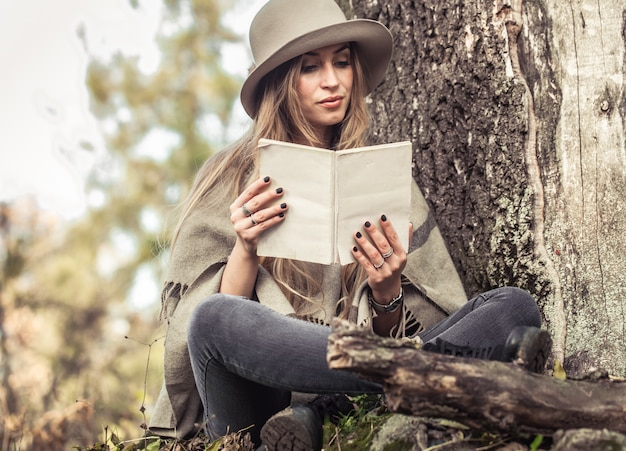 Девушка в шляпе читает книгу в осеннем лесу