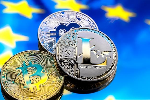 コインビットコインとライトコイン、ヨーロッパとヨーロッパの旗を背景に、仮想マネーのコンセプト、クローズアップ。