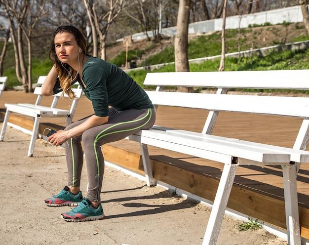 Девушка в спортивной одежде на скамейке слушает музыку