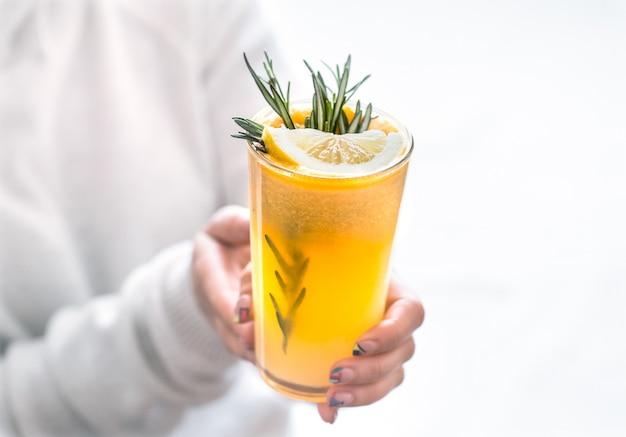 Девушка держит апельсиновый сок