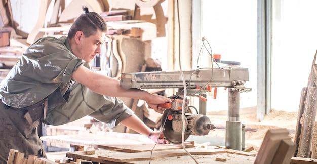 男は木製の製品で機械で作業します