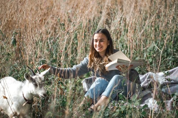 Молодая девушка на поле читает книгу