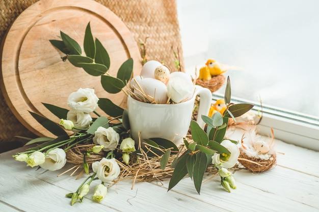 ハッピーイースターの背景。窓の近くの花の装飾が付いている巣のイースターエッグ。ウズラの卵。ハッピーイースターのコンセプト