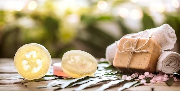 スパ手作り石鹸とタオル、熱帯の組成の葉の木製の背景