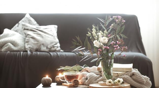 花とキャンドルの花瓶のある居心地の良いホームインテリアリビングルーム