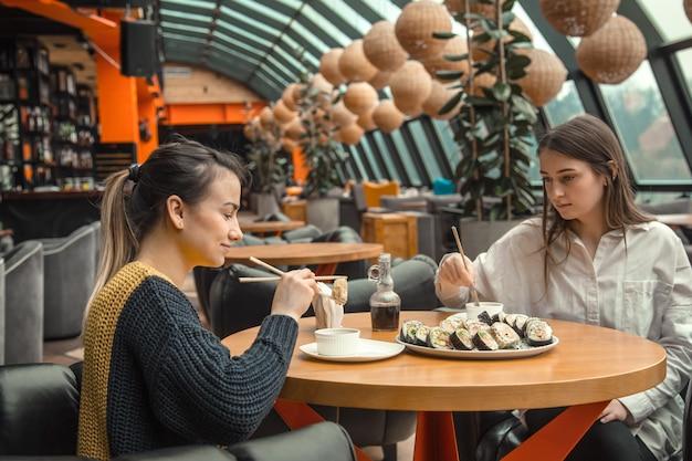 Две счастливые женщины сидят в кафе, едят суши