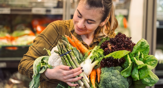Органические овощи крупным планом. красивая молодая женщина, покупки в супермаркете и покупка свежих органических овощей