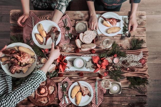 Плоские руки друзей едят и пьют вместе. вид сверху людей, имеющих вечеринку, сбор, празднование вместе за деревянным деревенским столом