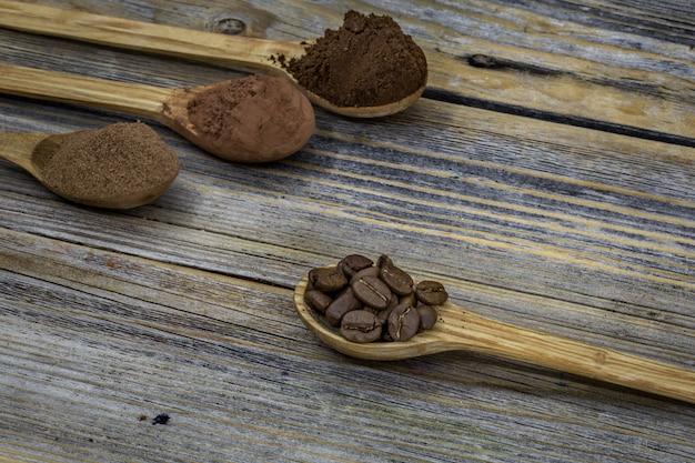 Красивая маленькая деревянная ложка с кофе на фоне
