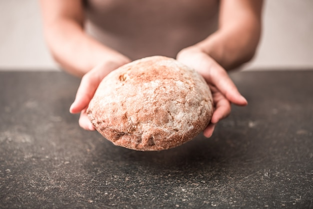 手のクローズアップで焼きたてのパン