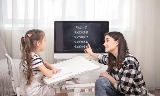 子供を持つ母親がテーブルに座って宿題をします。