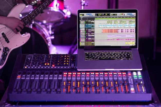 音楽を録音するコンピューターを備えたレコーディングスタジオのデジタルミキサー。