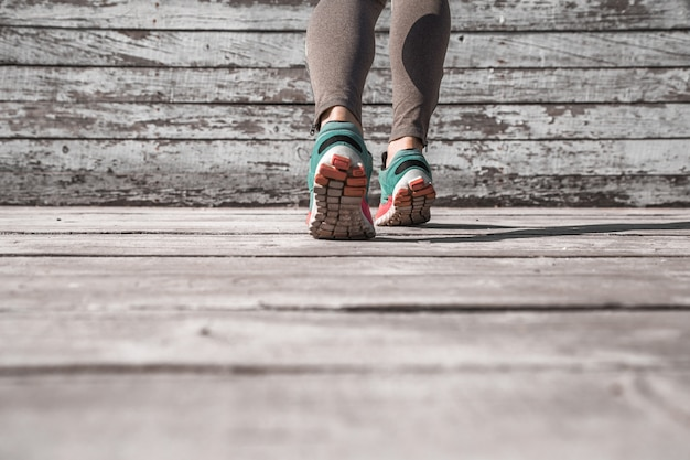 Женские ножки в кроссовках на деревянном столе