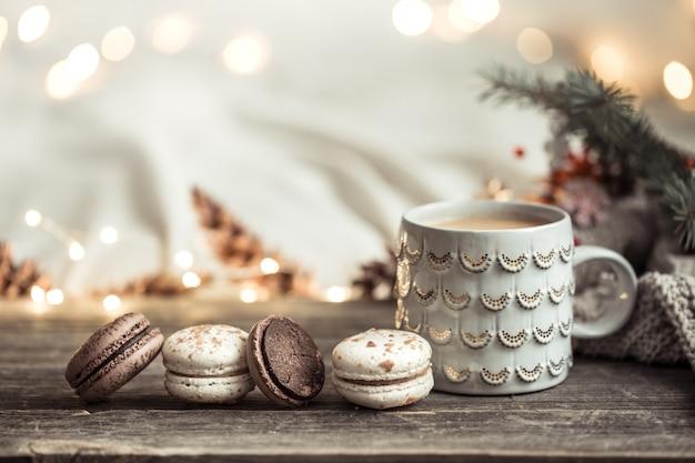 ライトとお祝いの装飾が施された木の上でカップとマカロンのデザートでお祝い。自宅の居心地のよさと快適さ