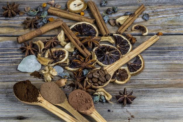 Красивое расположение сушеных лимонов, корицы, кофе на деревянных ложках на дереве