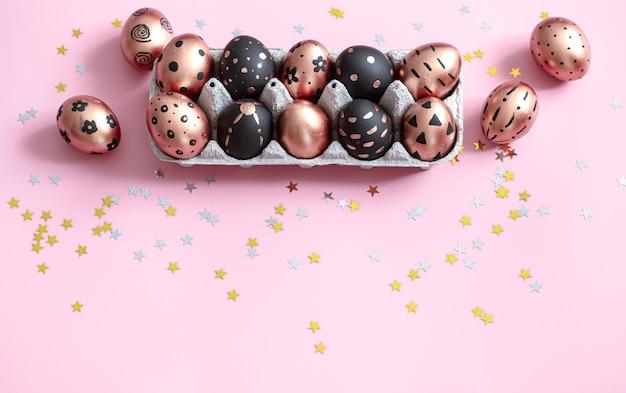 Праздничная роспись золотыми и черными пасхальными яйцами на розовом.