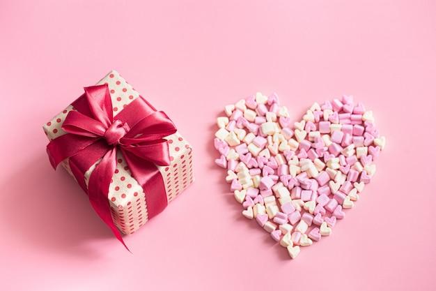 Концепция дня святого валентина. подарочная коробка с красным бантом на розовый.