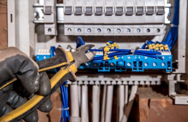 電気パネルの組み立て、電気技師の仕事、ワイヤーと回路ブレーカーを備えたロボット