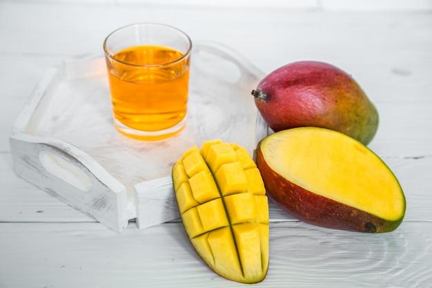 ジュースと白い木製のテーブルのマンゴー