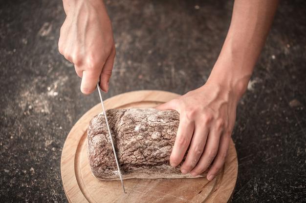 古い木製のテーブルの手のクローズアップで焼きたてのパン