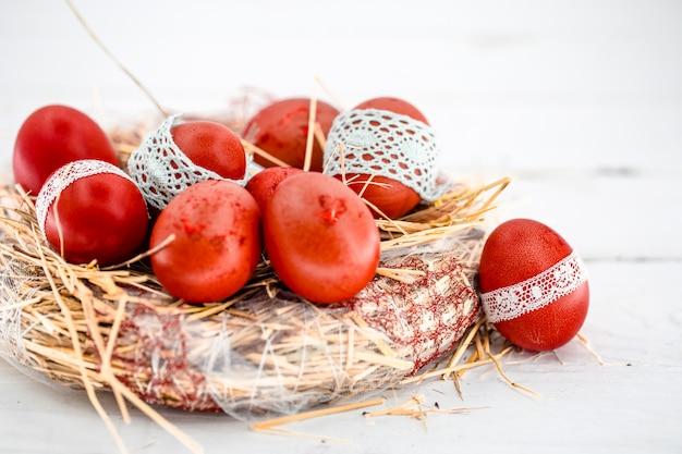 Красные пасхальные яйца в гнезде сена