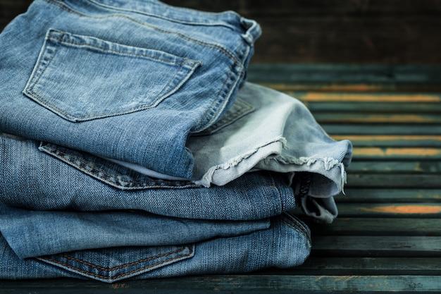 木製のテーブル、流行の服にジーンズの束