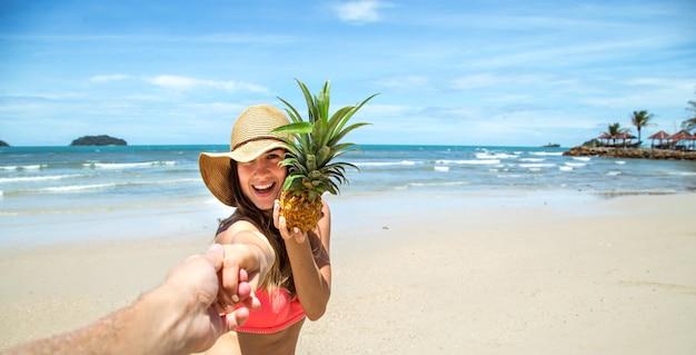Красивая девушка в купальнике и ананасе гуляет по пляжу, держа за руку парня